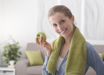Femme mangeant une pomme après son jogging avec une bonne nutrition